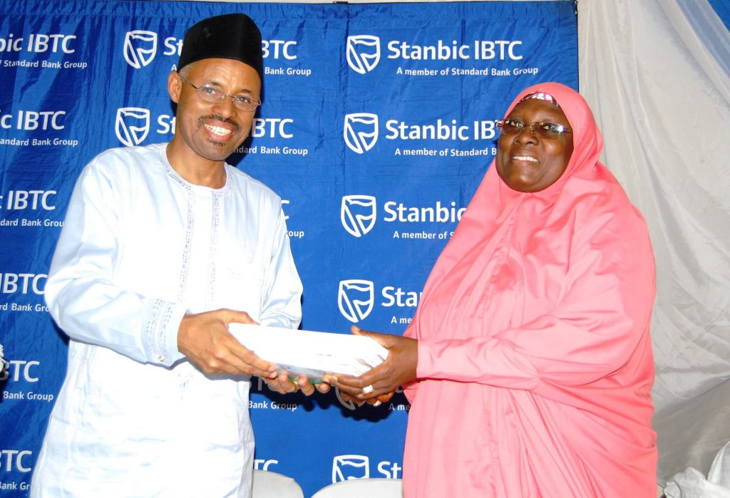 Head, Public Sector Group, Mr. Yusufu Modibbo, Stanbic IBTC Bank, presenting financial literacy books from the Central Bank of Nigeria to the Principal, Government Girls Secondary School, Maimuna Gwarzo, Tudun Wada, Kaduna State, Hajiya Hassana Usman, during an event organised by Stanbic IBTC to mark the 2016 Financial Literacy Day at GGSS Kaduna on Thursday, 17 March, 2016.